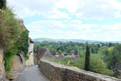 Vue panoramique sur un village et une vallée couverte d'arbres