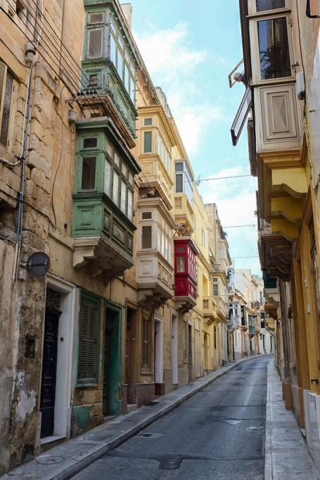 Une rue de Kalkara avec les balcons maltais en bois de différentes couleurs