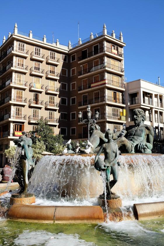 Une fontaine et un immeuble sur une place de Valence