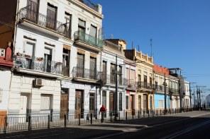 Des maisons colorées et une personne qui marche sur le trottoir