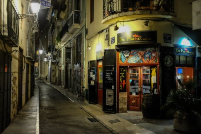 Une ruelle sombre avec des bars et des restaurants